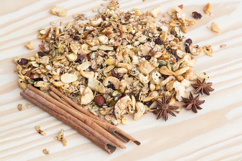 La pila de palillos del cereal y de canela del granola en el backgroun de madera foto de archivo