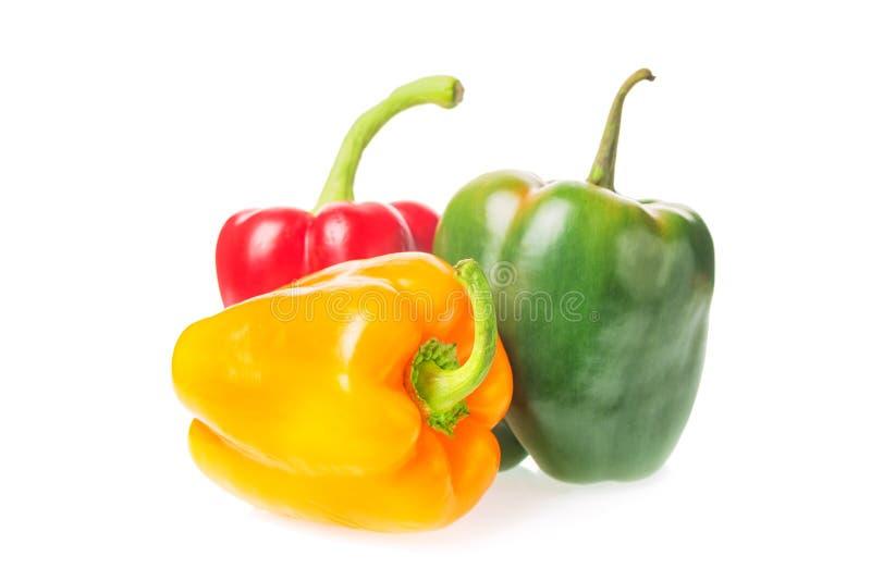 La pila de paprikas coloridos amarillea, roja y verde paprika aislada en el fondo blanco foto de archivo