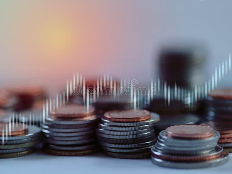La pila de plata y de bronce acuña la capa con el gráfico de las divisas del mercado de acción en fondo de la falta de definición fotografía de archivo libre de regalías