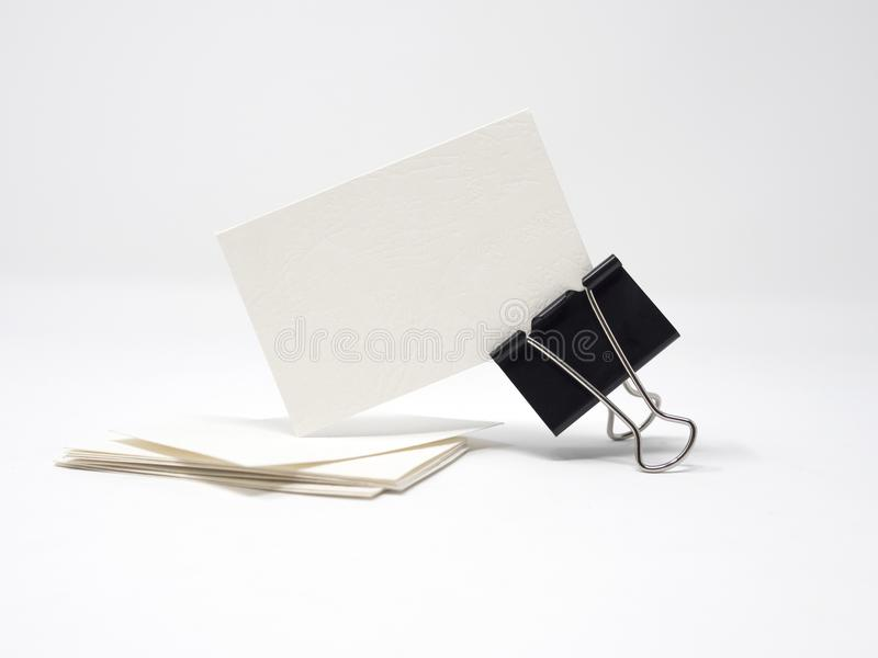 La pila de tarjetas de visita en blanco y una tarjeta de visita en blanco se sostuvieron al lado del clip de la carpeta foto de archivo
