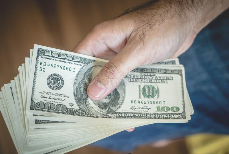 La pila de la tenencia de la mano de dólar observa la visión superior foto de archivo