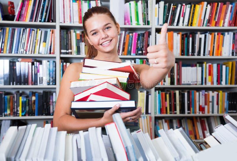 La pila de la tenencia de la muchacha del adolescente de demostraciones de los libros golpea pesadamente para arriba en una libre fotos de archivo libres de regalías