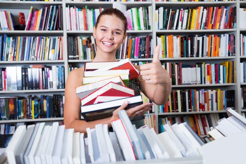 La pila de la tenencia de la muchacha del adolescente de libros muestra golpe para arriba en un booksto foto de archivo