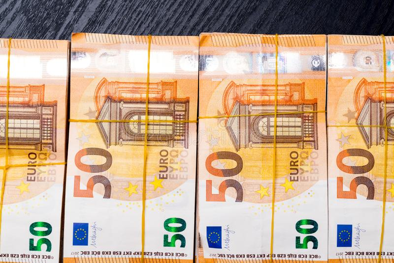 La pila del euro real 50 observa 50 billetes de banco euro debajo de la goma aislada en negro Valor de cerca de 20000 euros foto de archivo libre de regalías
