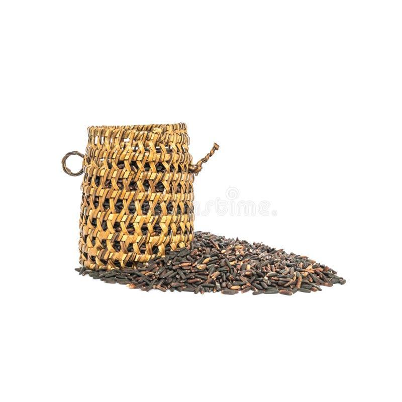 La pila del primer de arroz negro llamó el arroz riceberry con la cestería de madera, arroz con los altos alimentos aislados en e fotos de archivo libres de regalías