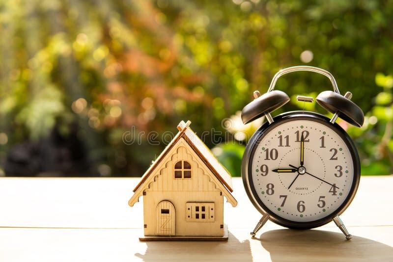 La pila della sveglia e della casa sul fondo di legno di tramonto e della tavola nel pacchetto e nel concetto pubblici di affari fotografia stock