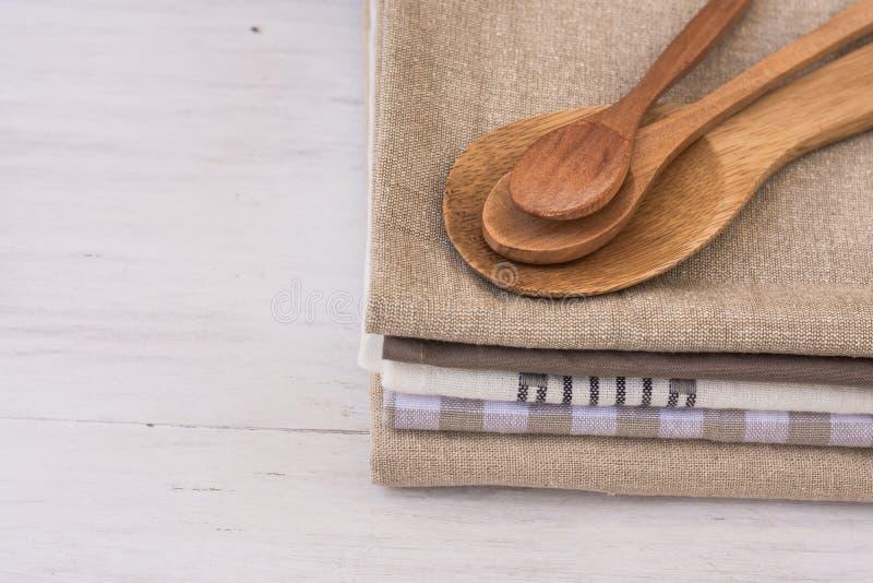 La pila di asciugamani di cucina di tela del cotone, di legno fatto a mano dà, sul tavolo da cucina bianco, lo stile a cucchiaiat immagini stock
