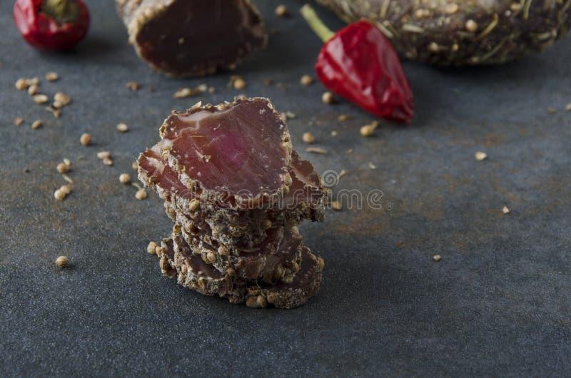 La pila di fette ha asciugato la carne con le spezie sulla tavola grigia fotografia stock libera da diritti