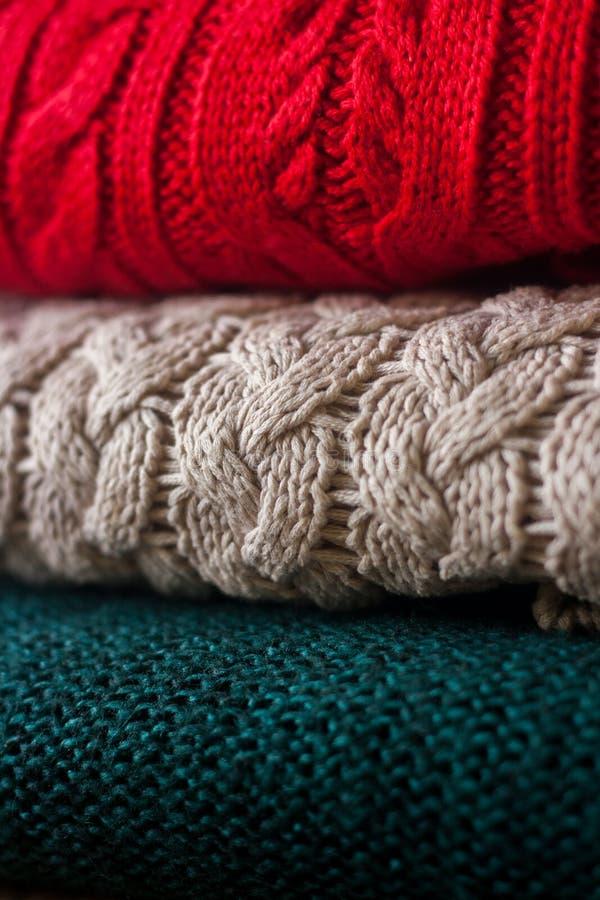 La pila di maglioni tricottati caldi si chiude su Fondo variopinto accogliente fotografie stock libere da diritti