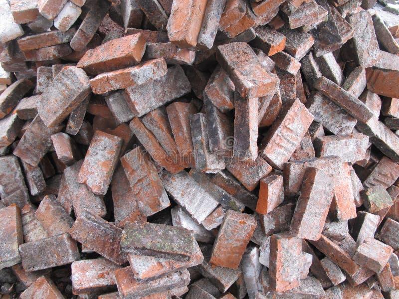 La pila di mattoni rossi rotti sulla terra, vecchi mattoni struttura il fondo immagini stock