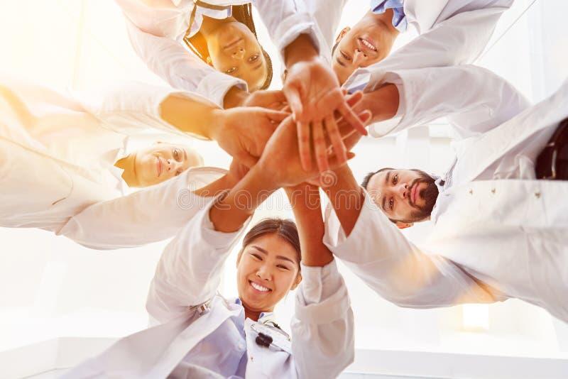 La pila di medici passa insieme come gruppo per la motivazione fotografia stock libera da diritti