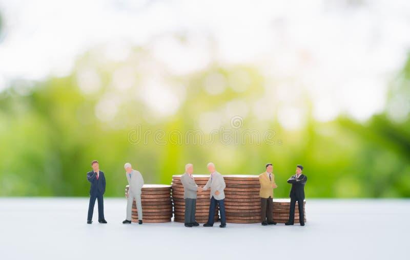La pila di monete dietro handshake miniatura dell'uomo d'affari, discute fotografia stock libera da diritti