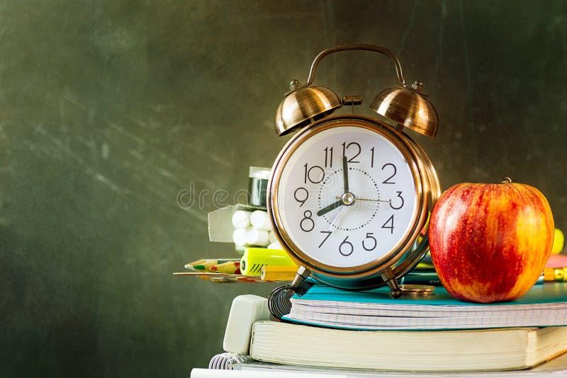 La pila di penne dei libri di esercizi disegna a matita la mela rossa della sveglia sul fondo graffiato d'annata della lavagna Di immagine stock libera da diritti