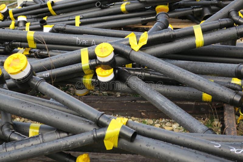 La pila di tubi neri del tubo tiene insieme con nastro adesivo giallo fotografie stock