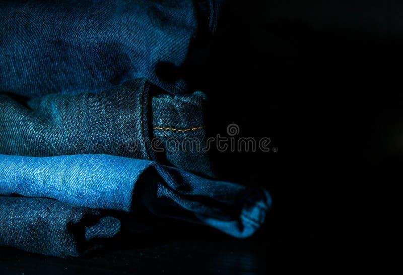 La pila di vestiti piegati, blue jeans ansima, pantaloni blu scuro del denim su fondo scuro immagine stock