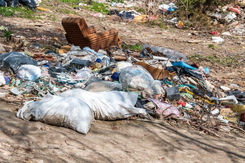 La pila grande de desperdicios y de basura descargó en la naturaleza o el parque en la ciudad que contaminaba el ambiente con el  fotos de archivo