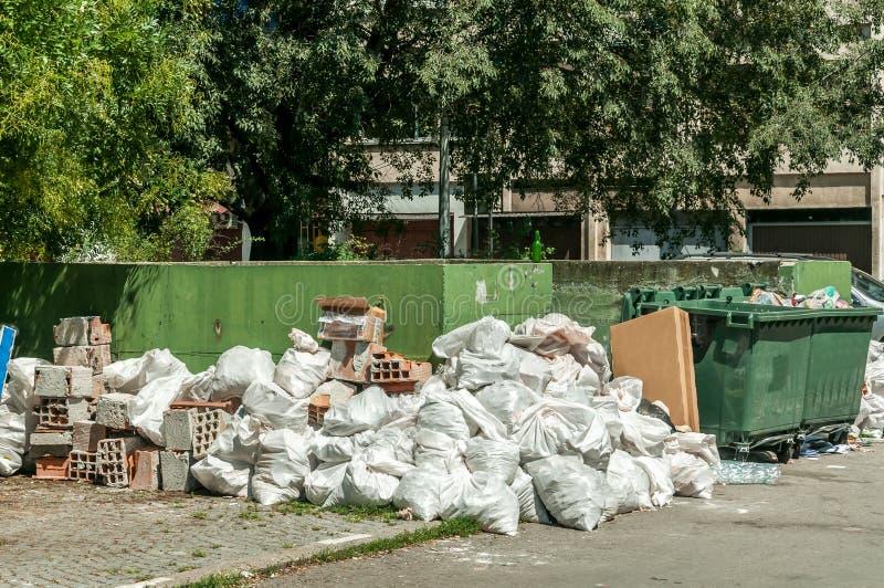 La pila y la pila grandes de basura y de desperdicios en las bolsas de plástico acercan a las latas del contenedor en la calle en foto de archivo