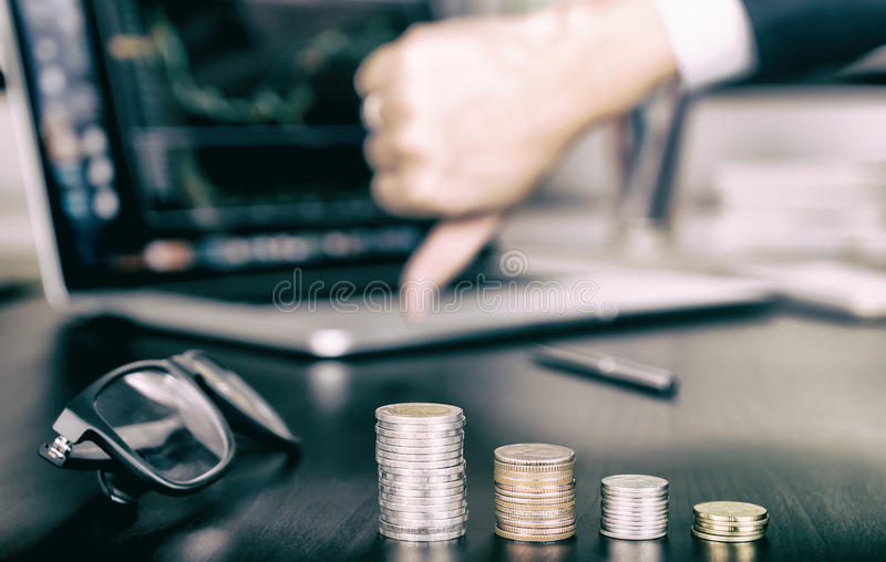 La pile d'argent de pièce de monnaie descend en tant qu'échouer courant, pouce vers le bas photographie stock