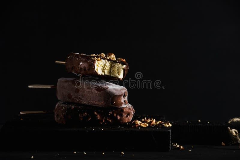 La pile de chocolat a plongé des glaces à l'eau avec les écrous ébréchés sur le conseil en bois foncé au-dessus du fond noir photographie stock