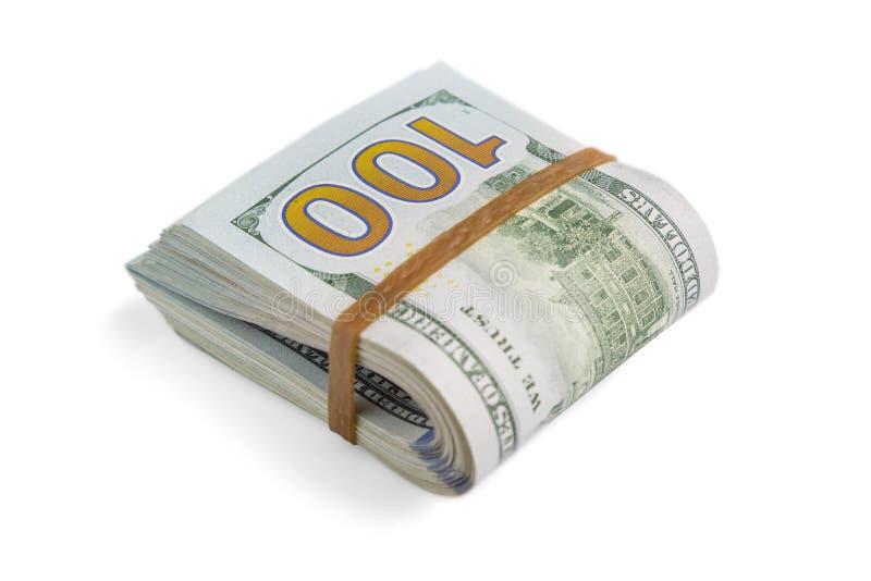La pile de dollars d'argent liquide, penchant dans la moitié, sous la bande élastique est isolée sur un fond blanc Plan rapproché images libres de droits