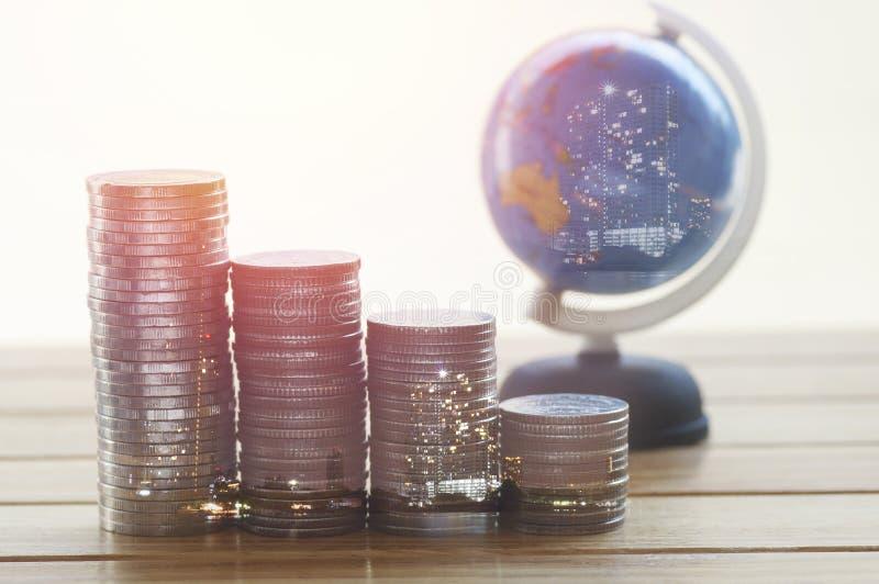 La pile de l'argent invente avec le globe sur la table, pour l'investissement de construction de concept photographie stock libre de droits