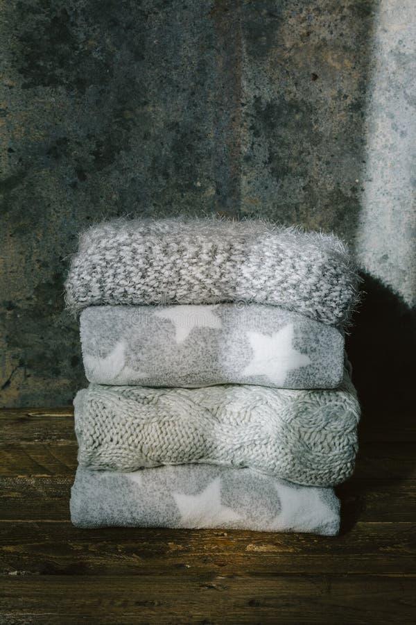 La pile de l'hiver tricoté vêtx sur le fond en bois images stock