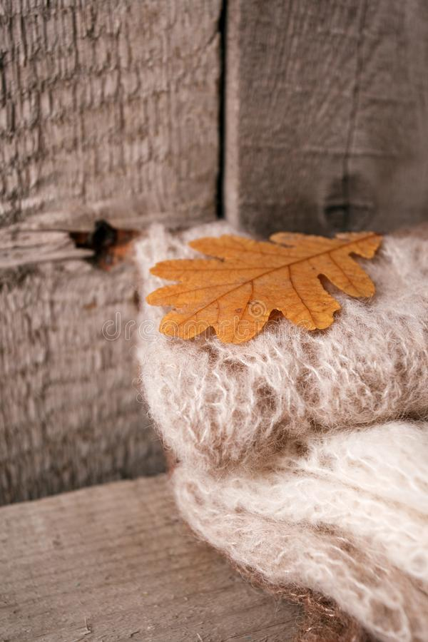 La pile de l'hiver tricoté vêtx sur le fond en bois, chandails, tricots, les feuilles de jaune, l'espace pour le texte, concept d photos stock