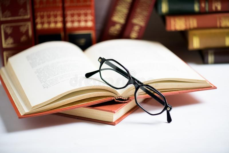 La pile de livres avec les verres des hommes de couleur a placé sur le livre ouvert dans la bibliothèque ou sur la table blanche photo stock