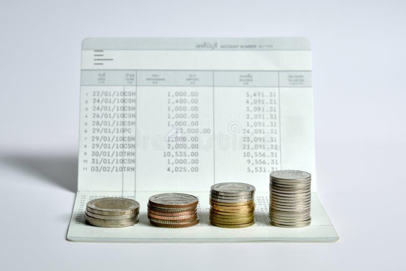 La pile de pièces de monnaie intensifient sur le livre de comptes d'économie de banque photo libre de droits