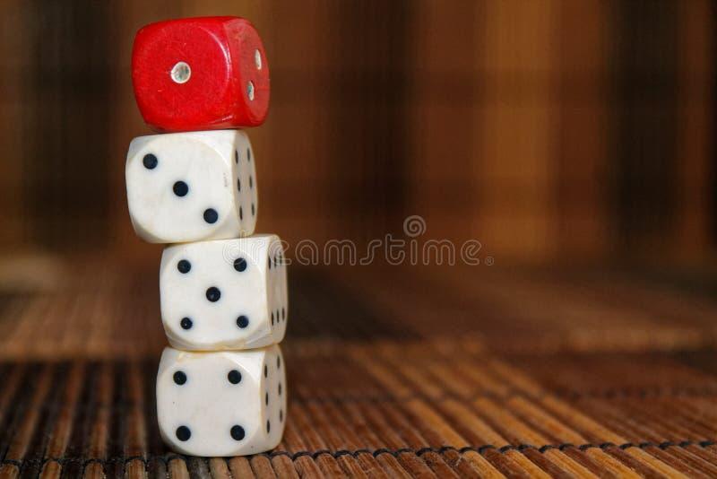 La pile de plastique de trois blancs découpe et une matrice rouge sur le fond brun de conseil en bois Six cubes en côtés avec les photos stock