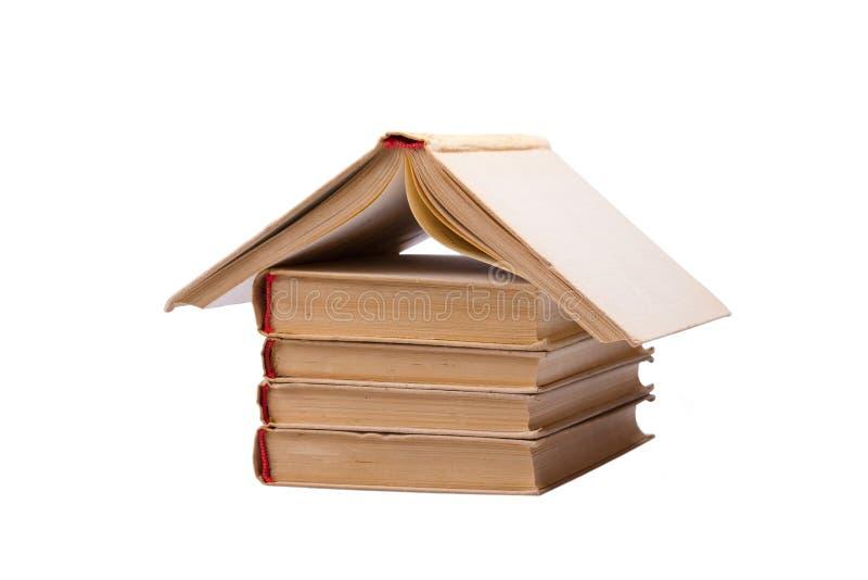 La pile des livres avec un s'est ouverte comme le toit de maison images stock