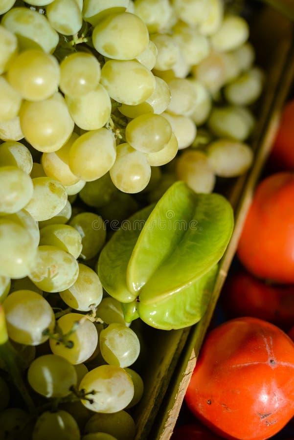 La pile des raisins et le carambolier se sont vendus au marché de fruit image stock