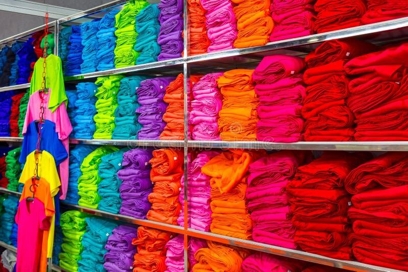 La pile des T-shirts colorés pliés vêtx d'une boutique photos stock