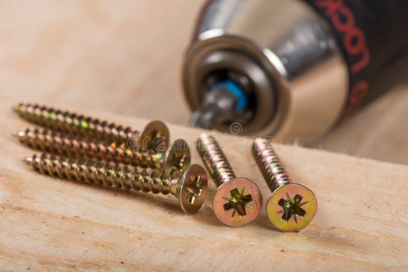 La pile des vis en métal pour le bois avec l'accu forent dedans le fond photo libre de droits