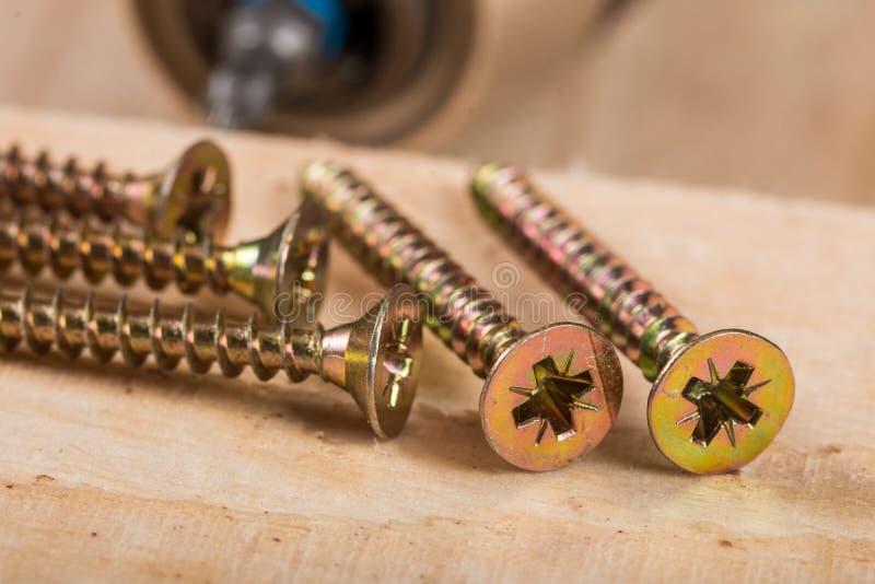 La pile des vis en métal pour le bois avec l'accu forent dedans le fond photographie stock libre de droits