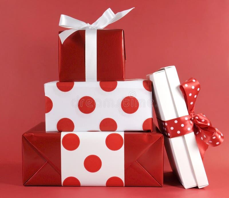 La pile du boîte-cadeau de fête de polka de thème rouge et blanc de point présente image libre de droits