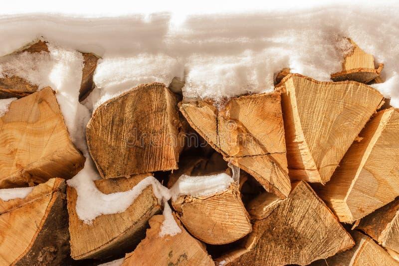 La pile du bois de chauffage coupé empilé couvert de neige, se ferment  photo libre de droits