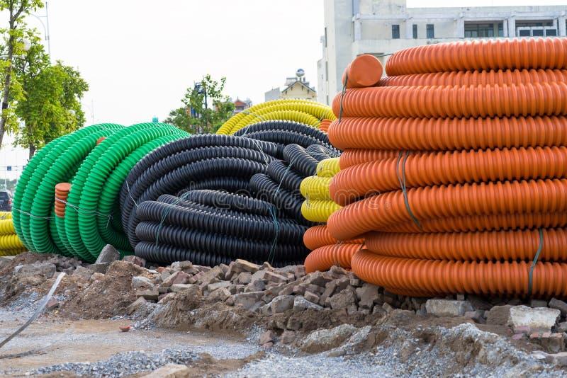 La pile du grand plastique industriel a ridé des tuyaux sur la terre photo stock