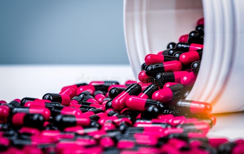 La pilule rose et noire de capsules s'est renversée du récipient en plastique blanc de bouteille Médicament délivré sur ordonnanc photographie stock libre de droits