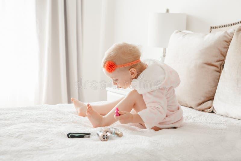 La pintura caucásica del bebé clava sentarse en cama en casa imagen de archivo