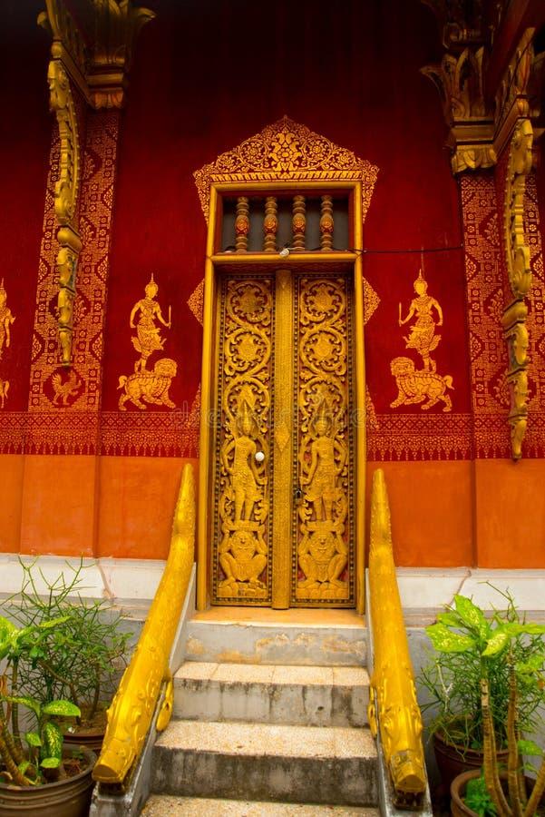 La pintura de la puerta y de pared Templo budista con oro Luang Prabang laos foto de archivo libre de regalías
