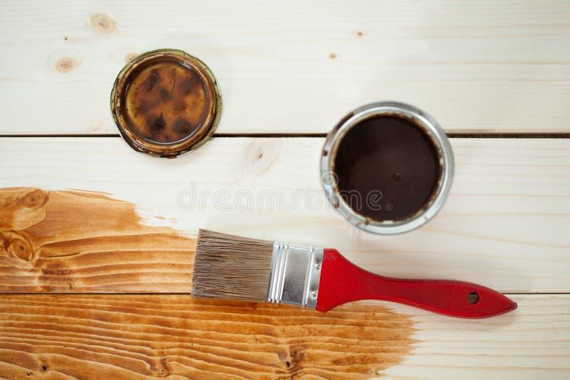 La pintura puede y brocha en tablones de madera imágenes de archivo libres de regalías