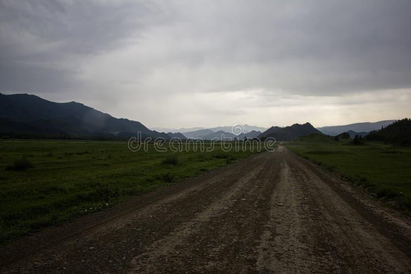 La pioggia si rannuvola la strada campestre in una valle della montagna fotografia stock libera da diritti