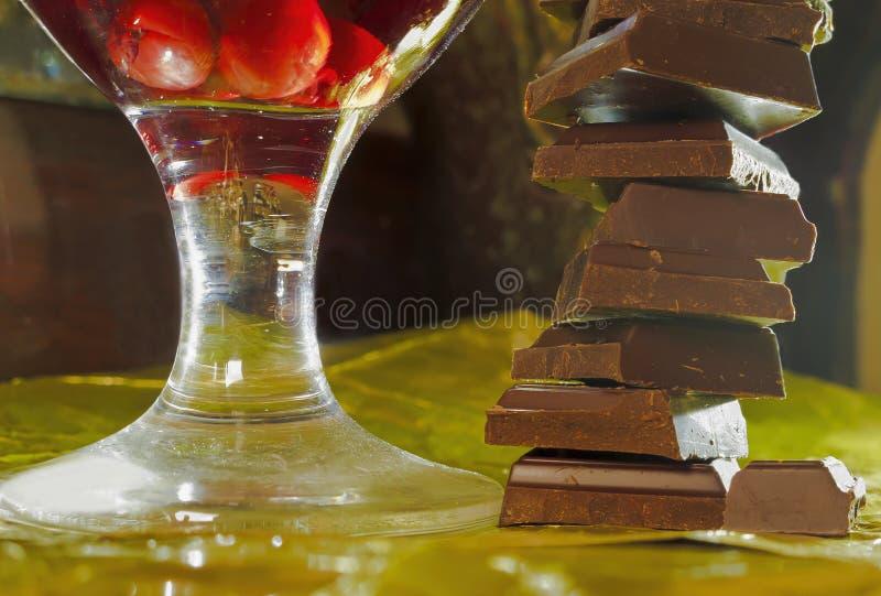 La pirámide de chocolates y un vidrio de la cereza wine imagenes de archivo