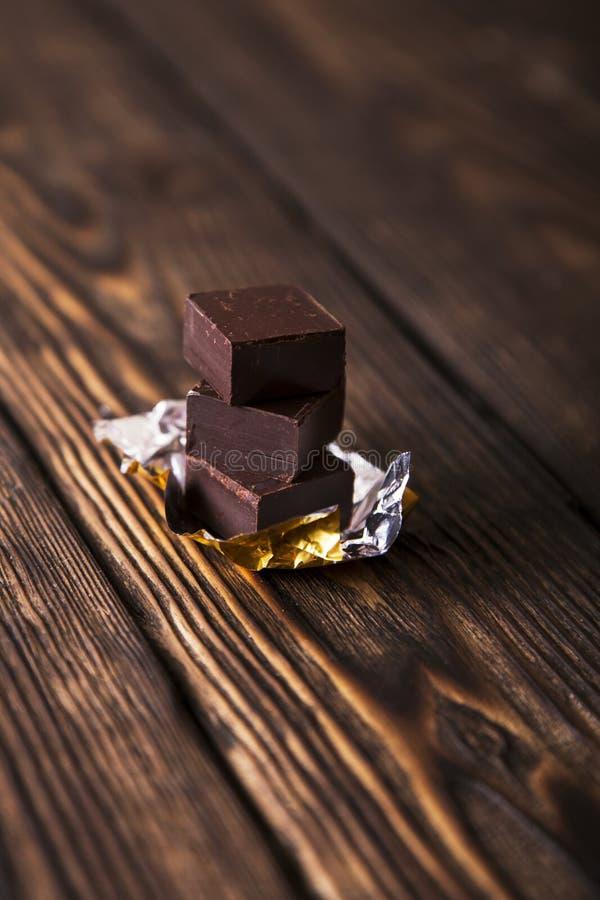La pirámide del chocolate negro junta las piezas en viejo fondo de madera oscuro imagenes de archivo