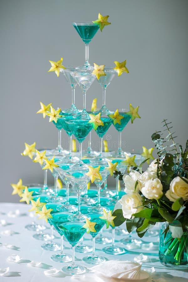 la piramide dei vetri con champagne e una carambola fotografia stock