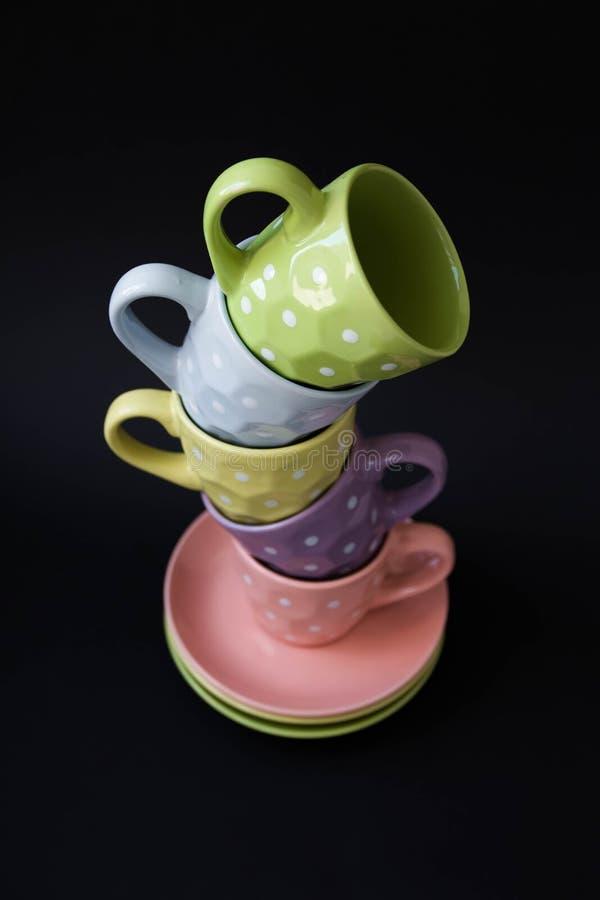 La piramide di tè ha colorato le tazze, su un fondo nero immagini stock