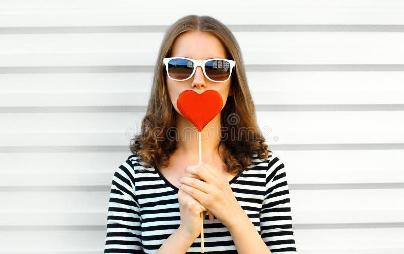 La piruleta en forma de corazón roja que se besa de la mujer del primer del retrato u oculta sus labios en la pared blanca imagen de archivo
