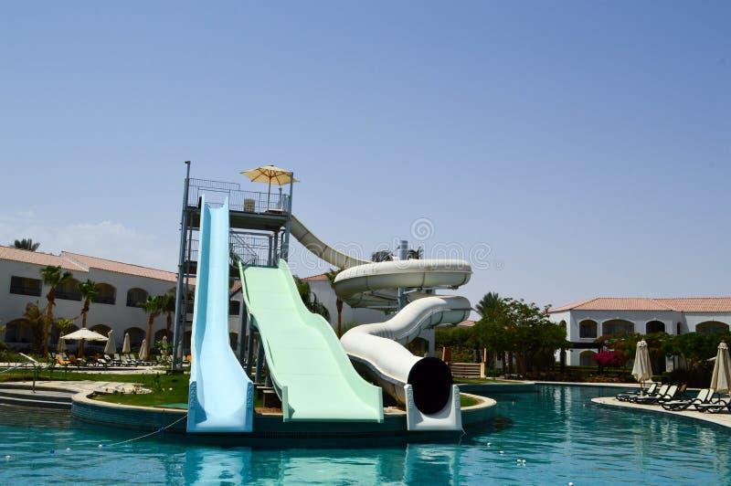 La piscina al aire libre con agua y los toboganes acuáticos calientes claros azules instala tubos el las vacaciones en un país ex foto de archivo