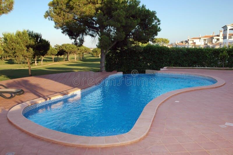 La piscina azul moderna con rojo teja la terraza - días de fiesta imagenes de archivo
